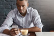 Handsome African office worker wearing checkered shirt with rolled up sleeves enjoying online communication, surfing internet on his mobile phone while having coffee during lunch at restaurant