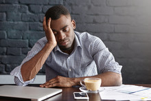 Frustrated Tired Young African-American Employee Touching His Head, Feeling Absolutely Exhausted Because Of Overwork, Calculating Accounts, Drinking Another Cup Of Coffee. Deadline And Overwork
