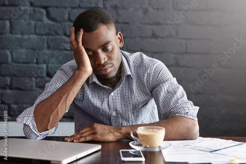 Fotografie, Obraz  Frustrated tired young African-American employee touching his head, feeling absolutely exhausted because of overwork, calculating accounts, drinking another cup of coffee