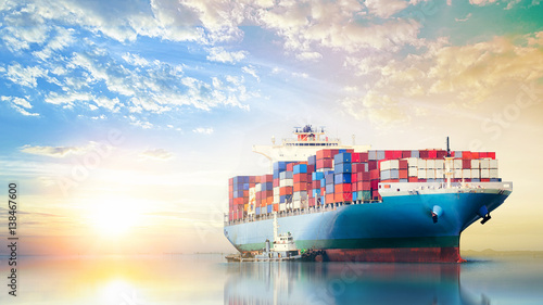 Fotografia  International Container Cargo ship in the ocean at sunset sky, Freight Transport