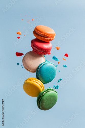 Poster Macarons Different types of macaroons in motion falling on light blue background.