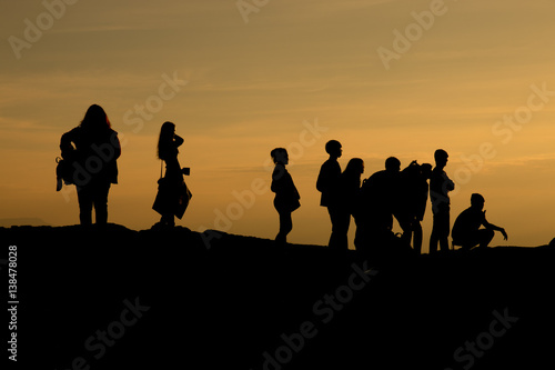 Foto op Canvas Militair silhouette of people relax at the cliff and mountains with sunset in the evening