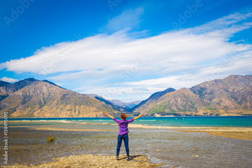 Photo  Woman embracing the view of Lake Hawea and mountains, NZ