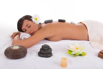 Obraz na płótnie Canvas Young woman receiving hot stone massage