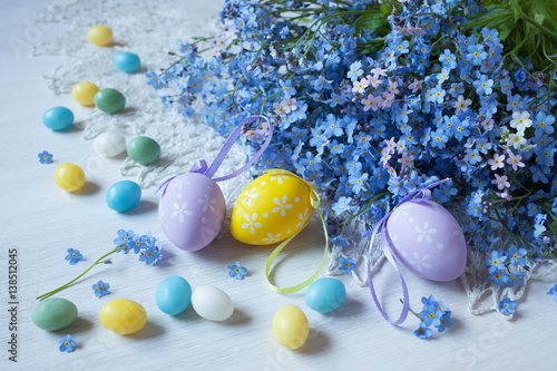 Easter eggs and blue flowers forget-me-not on the table
