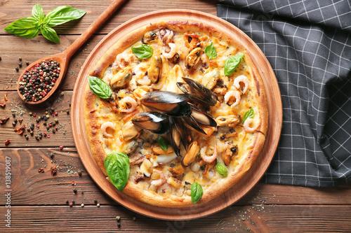Foto auf Gartenposter Gewürze 2 Gourmet seafood pizza and napkin on wooden background