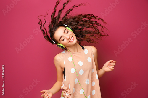 Photo  Beautiful young woman in headphones listening to music and dancing on color back