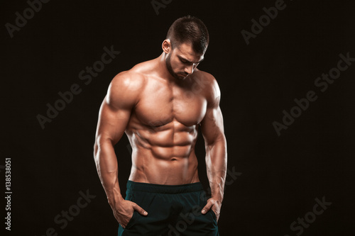 Fotografie, Obraz  Strong Athletic Man - Fitness Model showing his perfect back isolated on black b