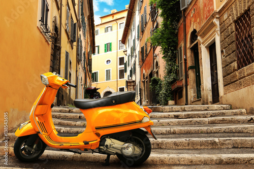 Photo Stands Rome Orange vintage scooter on the background of Rome street