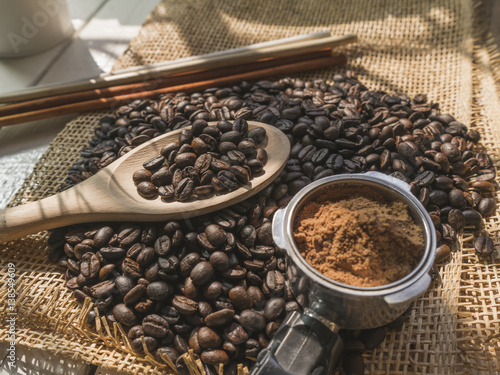 Fotobehang Koffiebonen Coffee bean on wood spoon and sack with coco powder on white wooden desk.