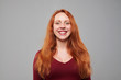 Happy woman with auburn hair looking at the camera