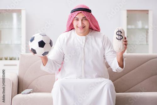 Poster  Young arab man watching football sitting on sofa