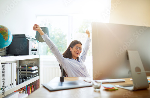 Woman celebrating something while seated at desk