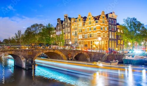 smugi-swiatel-statku-plywajacego-po-kanale-w-amsterdamie-w-godzinach-wieczornych