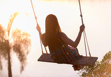 Silhouette Young Woman On A Swing With Sunset Background