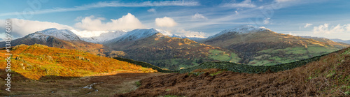 Fototapeta  Stunning snowcapped mountains with golden vibrant morning light in the Lake District