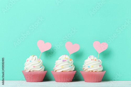 Tasty cupcakes on a green background Wallpaper Mural