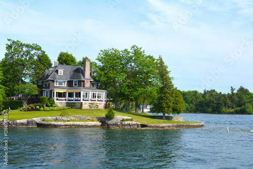 Fototapeta Island with house, cottage or villa in Thousand Islands Region in sunny summer day in Kingston, Ontario, Canada