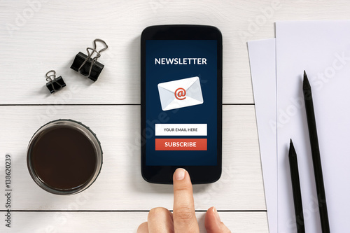 Fotografía  Subscribe newsletter concept on smart phone screen with office objects on white wooden table
