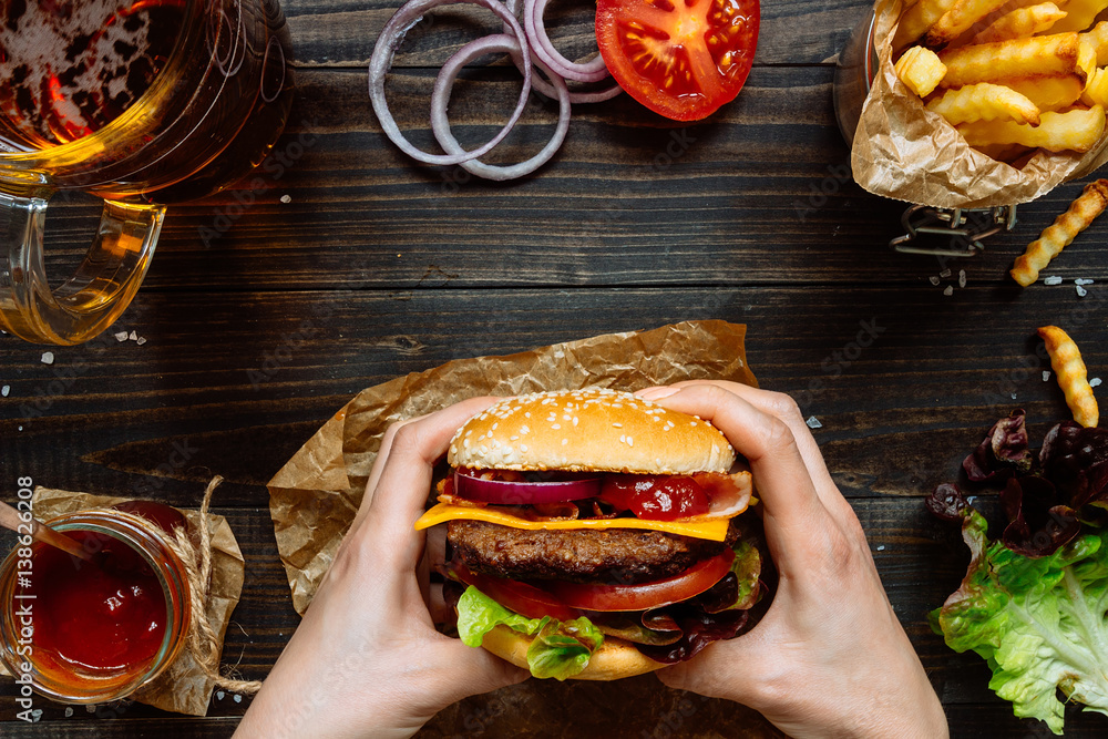 Fototapety, obrazy: Hands holding fresh delicious burgers with french fries, sauce and beer on the wooden table top view