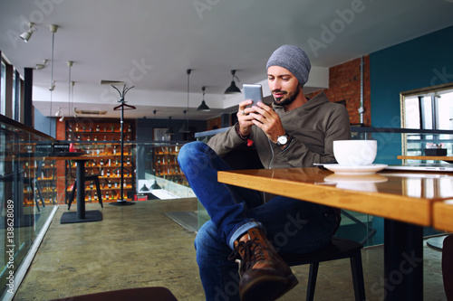 Young handsome hipster guy with beard texting with his mobile phone at the bar and having a cappuccino.