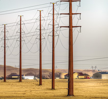 High Voltage Electric Pole Line In The Yellow Field, Meadow With Stormy Sky. Rural Landscape, USA.