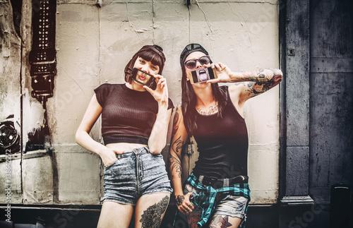 Fotografia  Portrait de deux jeunes femmes, le téléphone devant la bouche devant un mur en b