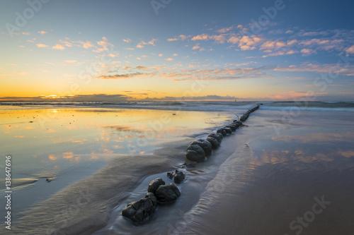 Foto auf Gartenposter Nordlicht Baltic sea at beautiful sunrise,wooden breakwater in the light of the setting sun
