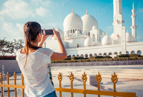Spoed Foto op Canvas Abu Dhabi Young tourist woman shooting on mobile phone Sheikh Zayed great white mosque in Abu Dhabi, United Arab Emirates, Persian gulf. UAE is famous tourism destination