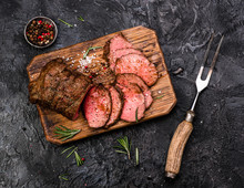 Sliced Grilled Roast Beef With Fork For Meat On Wooden Cutting Board. Black Background. Top View.