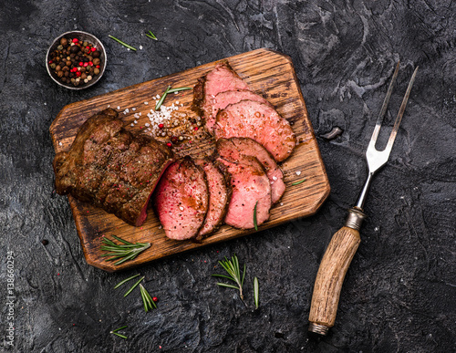 Sliced grilled roast beef with fork for meat on wooden cutting board Fototapeta