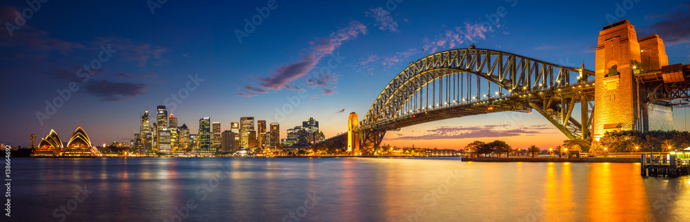 Fototapeta Sydney. Panoramic image of Sydney, Australia with Harbour Bridge during twilight blue hour.
