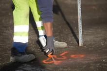Worker Marks A Spot On Asphalt With Florescent Spray Paint