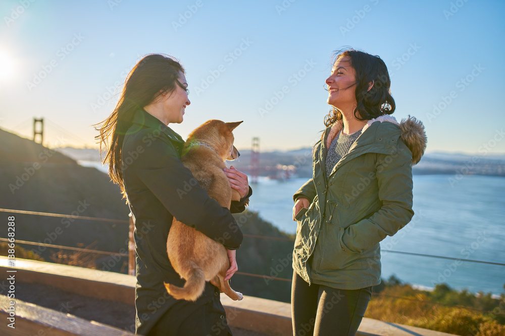 same sex lesbian couple with pet dog shiba inu on hills in front of ...