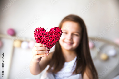 Beautiful little girl holding a red heart Canvas Print