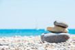 Relaxing in summer concept. Stones on the beach with boat on background.