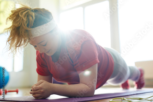Foto  Portrait of young obese woman working out on yoga mat in fitness studio: holding