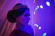 canvas print picture - Girl brunette in a red dress with beautiful hairstyle, earrings of beads and a crown on her head and bright makeup. Female style. Mysterious woman. Blue light