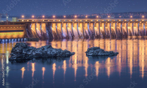 Poster Barrage Dam. Beautiful night industrial landscape with dam hydroelectric power station, bridge, river, city illumination reflected in water, rocks and blue starry sky in winter in Ukraine. Cityscape