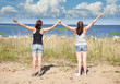 Two happy girls standing on the beach in summer