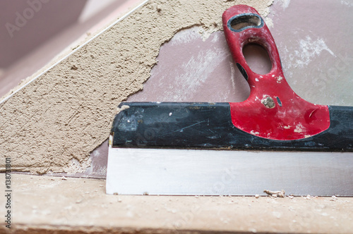 Fotografía  Repairing fireplace surface with spackle and trowel by hand