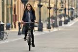 Fototapeta Miasto - Young woman on a bicycle.