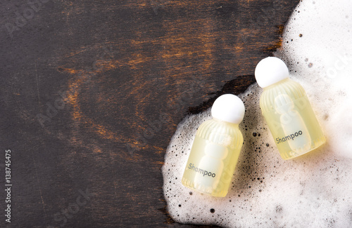 Fotografie, Obraz  Shampoo bottle with soap on wood,top view