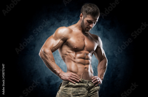 Canvastavla  Muscular young man in studio on dark background