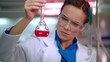 Lab flask with chemical liquid. Close up of woman chemist in lab. Closeup of female chemist studying chemical liquid in beaker. Serious chemist working with liquid in glass flask at laboratory