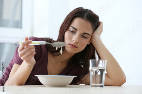 Depressed woman sitting at kitchen table without appetite Canvas Print