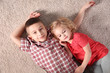 Cute little brother and sister lying on soft carpet