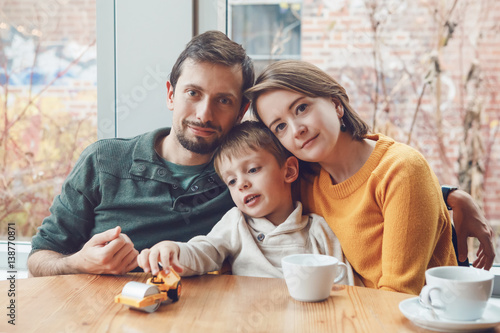 Photo  Portrait of white Caucasian happy family of three mother, father and son, sittin