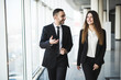 Confident business partners walking down in office and talking