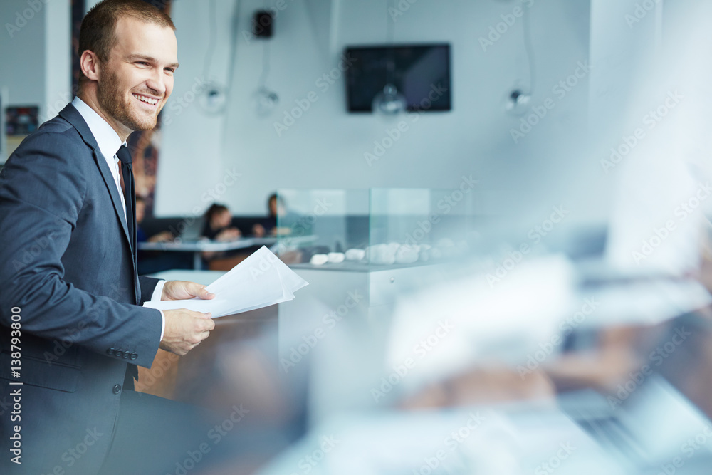 Fototapeta Handsome young businessman wearing formal attire standing up laughing, holding documents during coffee break in modern restaurant hall of office building